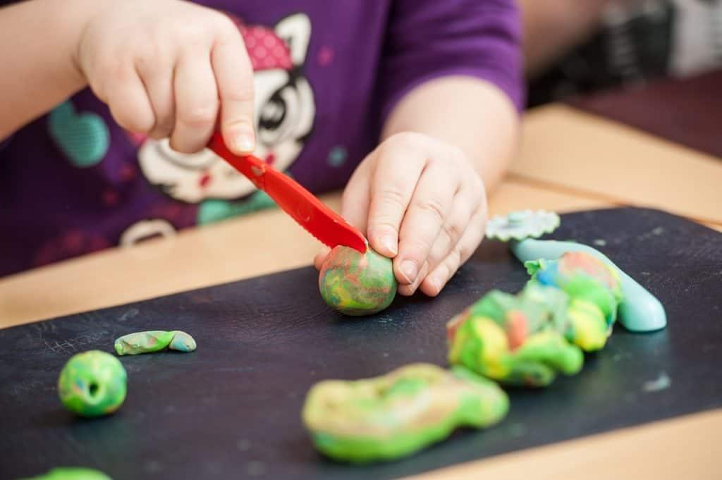 Mãos de criança usando uma faquinha na massinha de modelar.