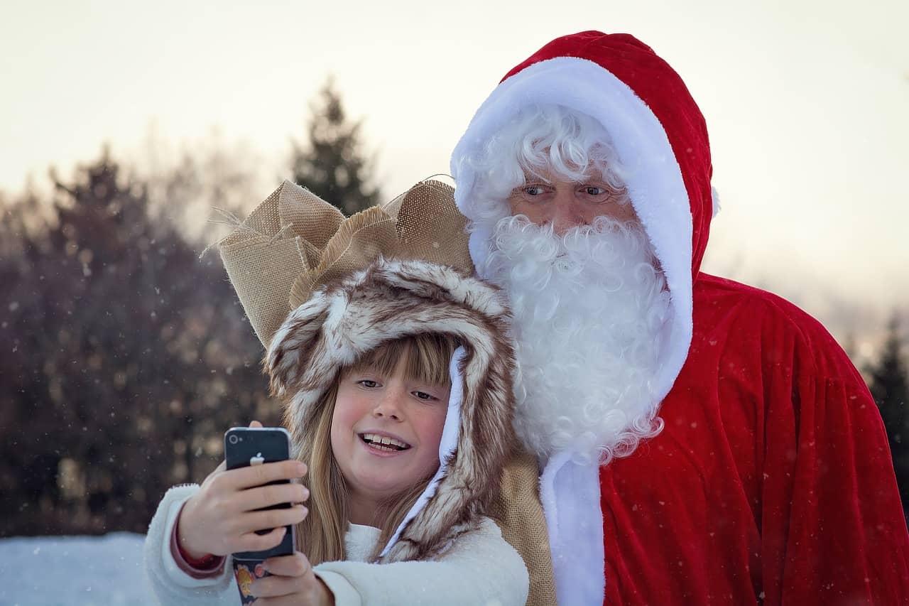 Criança tira selfie com papai noel na neve.