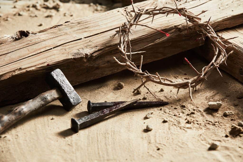Imagem com chão rústico onde estão um pedaço de madeira, um martelo, dois pregos bem grandes e uma coroa de espinhos.