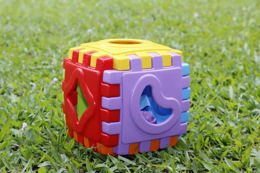 Na foto um bloco de brinquedo em cima de uma grama.
