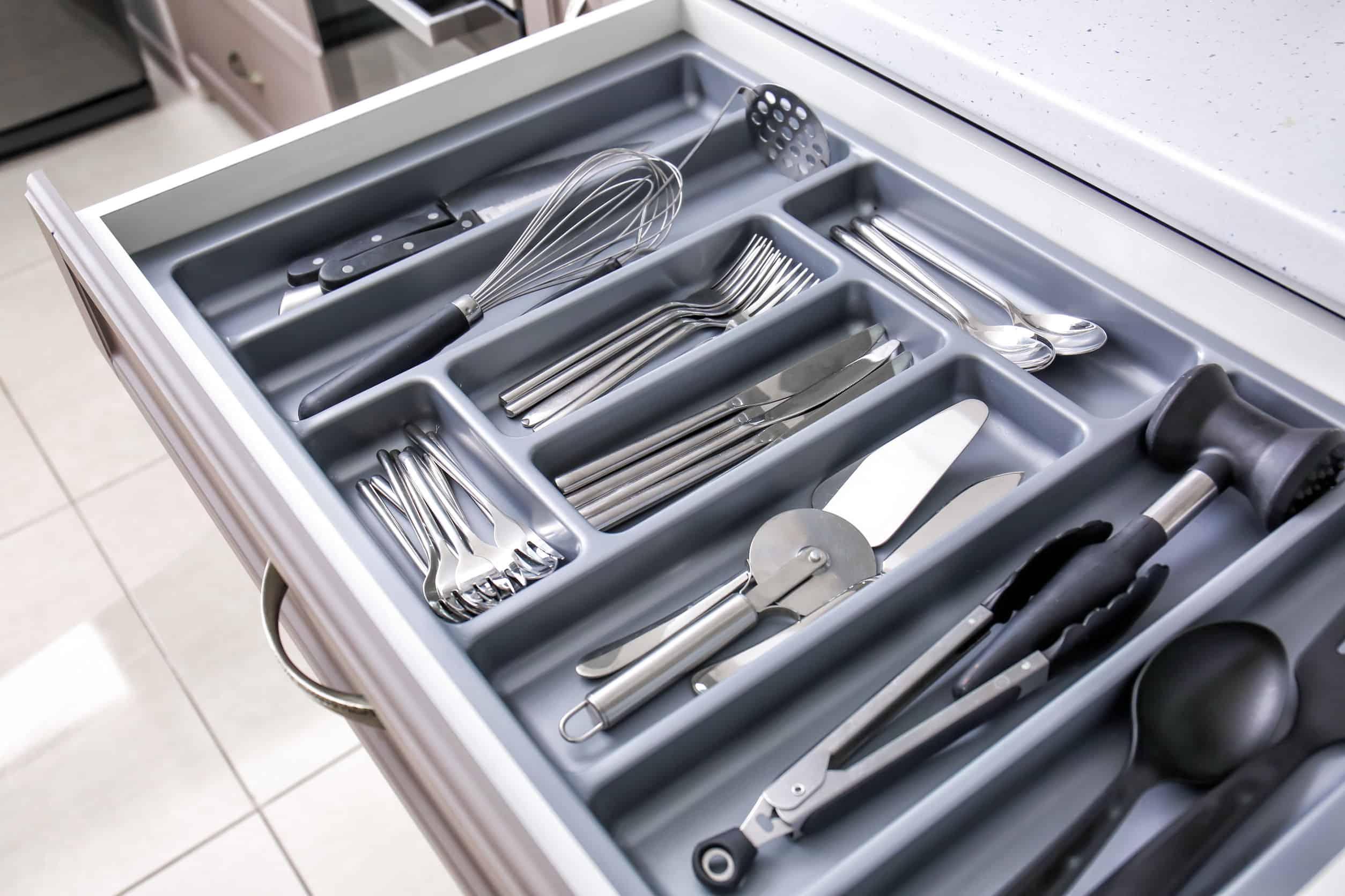 Talheres e utensílios organizados em divisor dentro de gaveta.