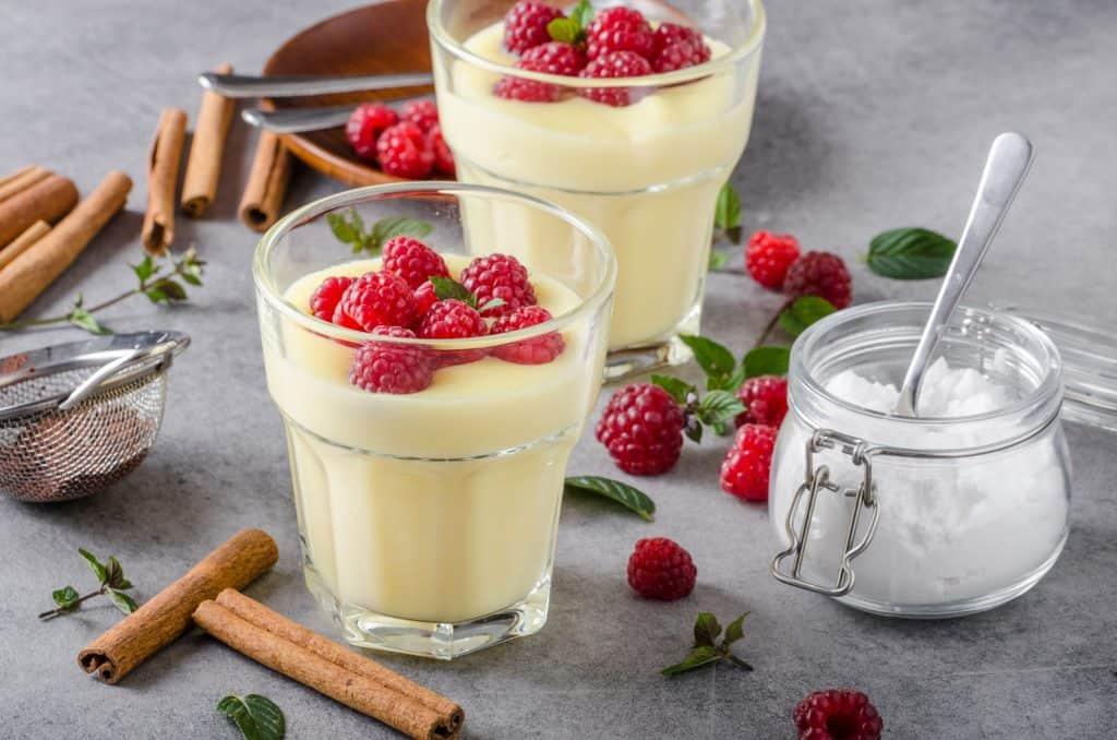 Dois copos com pudim com frutas vermelhas e canela ao redor e um açucareiro ao lado.