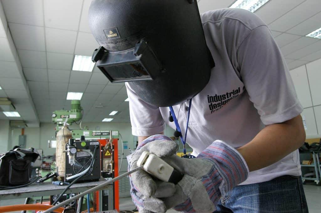 Imagem mostra uma pessoa usando uma máquina de solda com equipamentos de proteção.