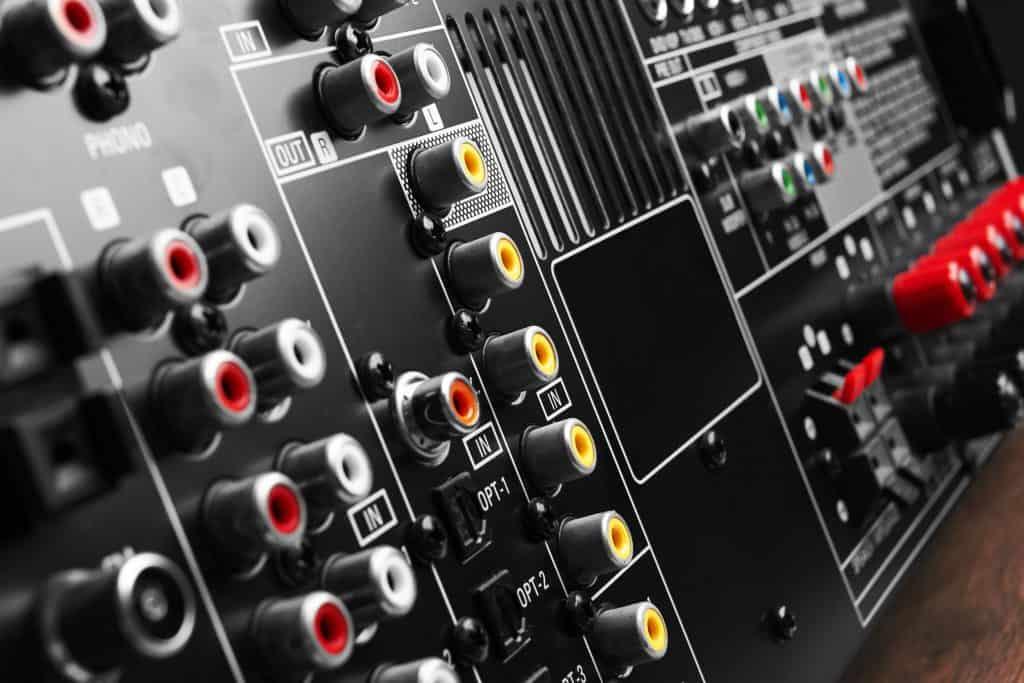 Imagem mostra a parte de trás de um receiver e diversas entradas e saídas.