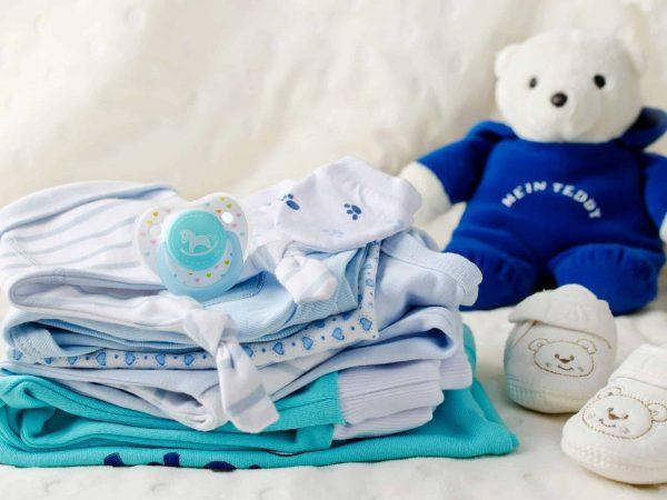 Na foto umas roupinhas de bebê com um sapatinho e um ursinho ao fundo.