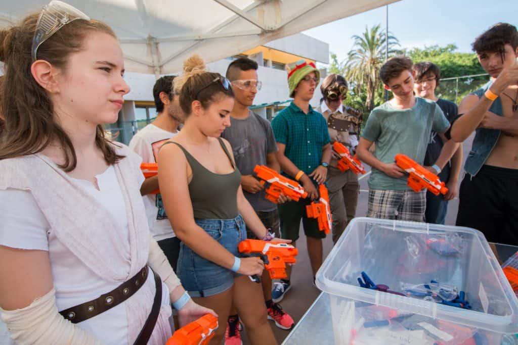 Jovens munidos com lançadores Nerf se preparam para batalha.
