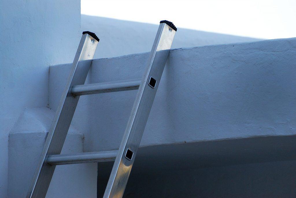 Imagem mostra uma escada de alumínio postada junto a paredes, levando a um andar superior.