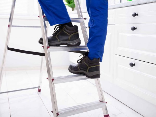 Pessoa subindo em escada de alumínio.