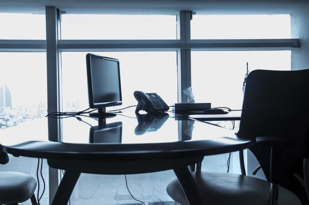 Na foto uma mesa de escritório com um telefone e um computador em cima em frente a janelas de vidro.