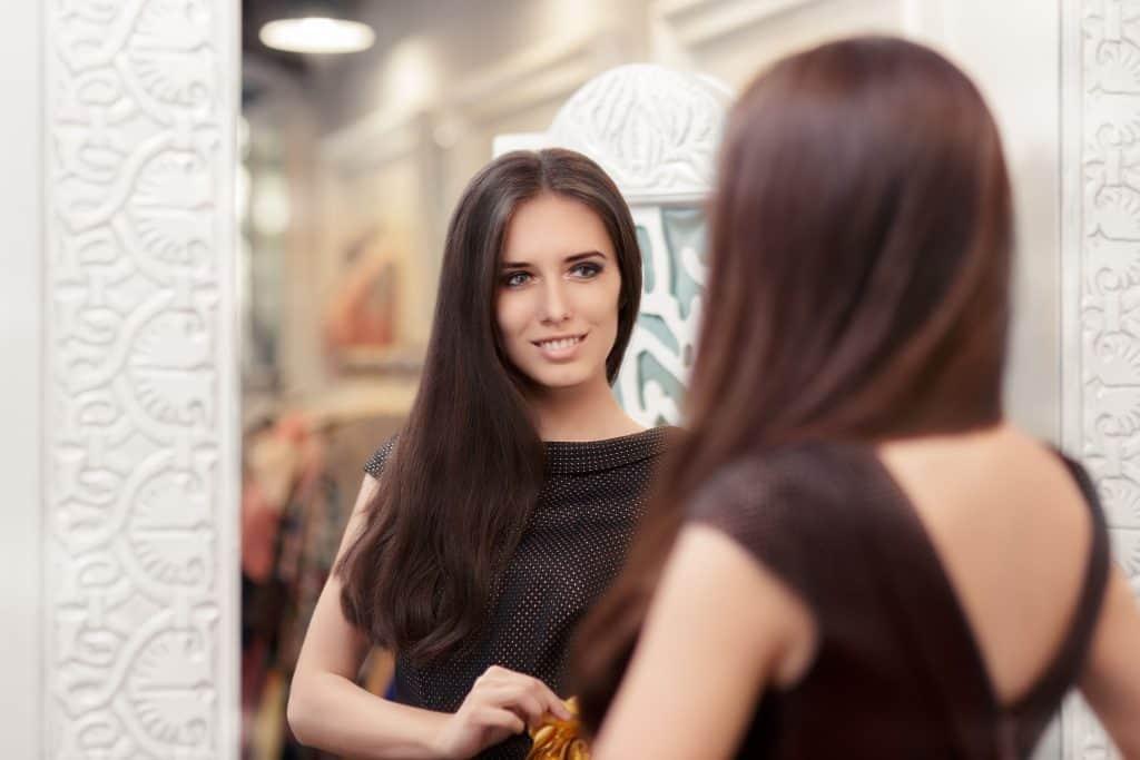 Imagem de mulher com vestido preto se olhando no espelho.