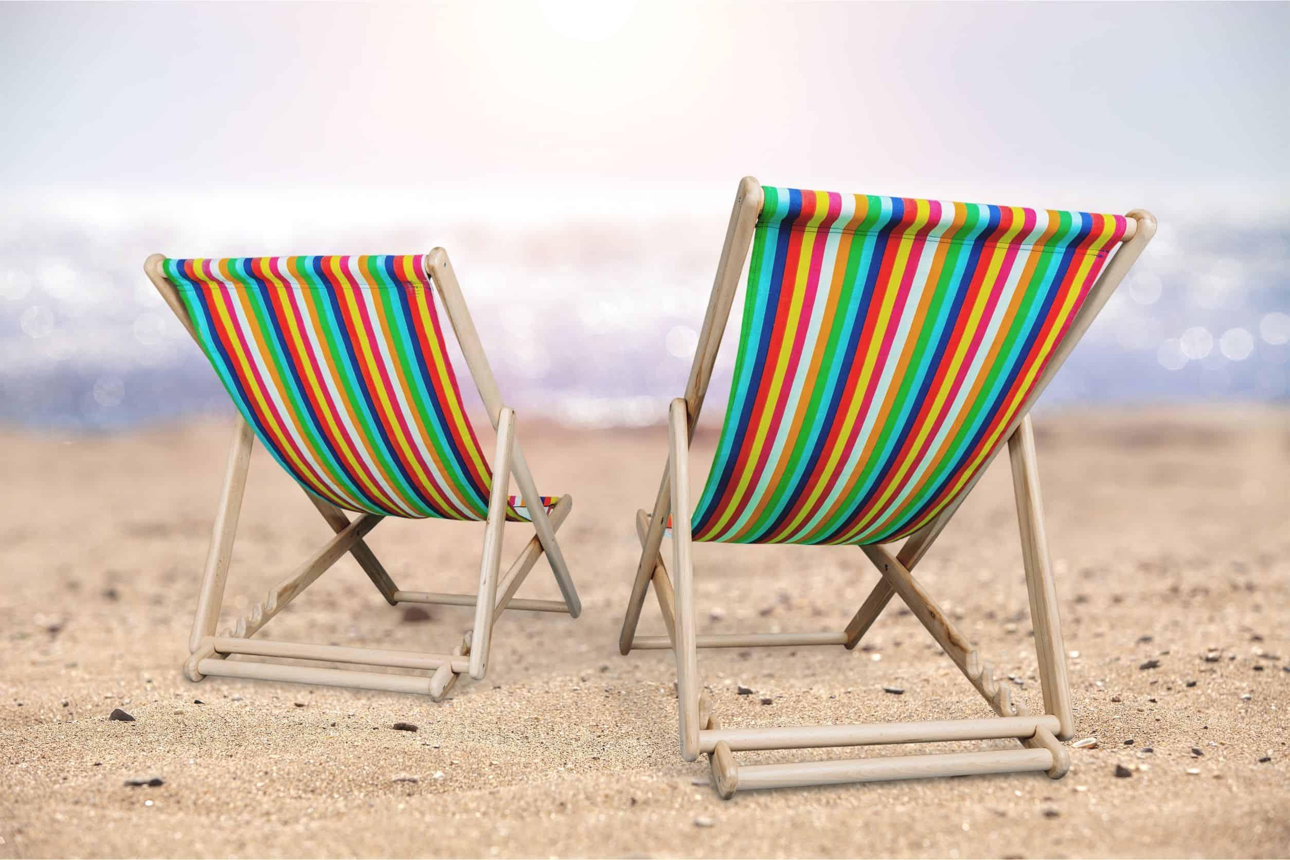 Imagem de duas espreguiçadeiras dobráveis na praia.