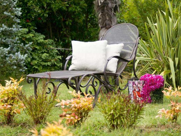 Na foto uma espreguiçadeira com almofadas ao lado de um cesto com flores e revistas no meio de um jardim.