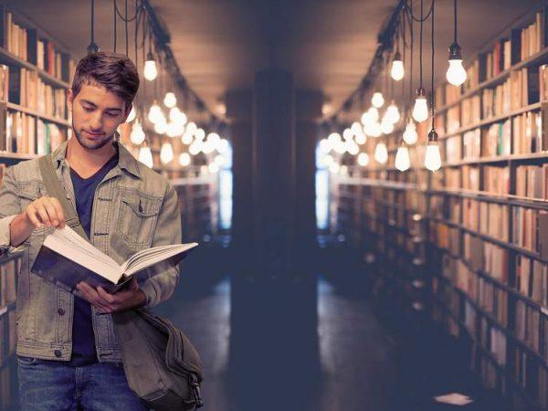 Imagem de um rapaz consultando um dicionário.