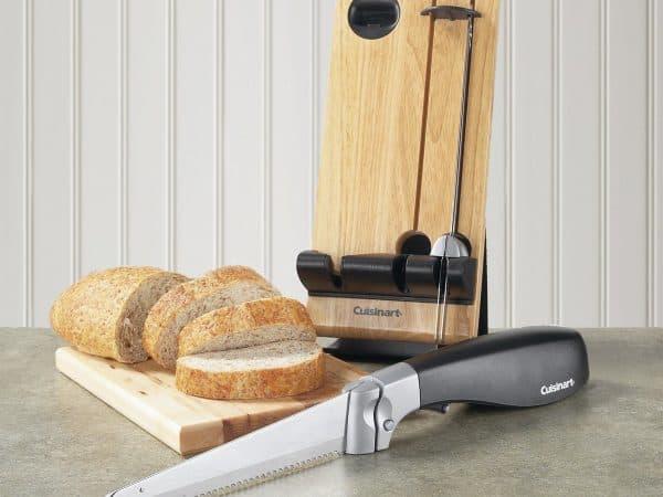 Imagem de uma faca elétrica ao lado de uma tábua de madeira com pão fatiado em cima.