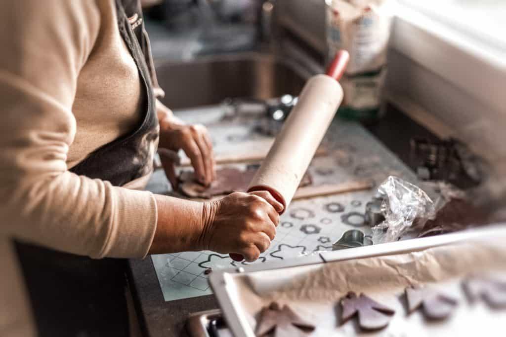 Imagem de mulher enquanto prepara biscoitos decorados com auxílio de rolo de massa.
