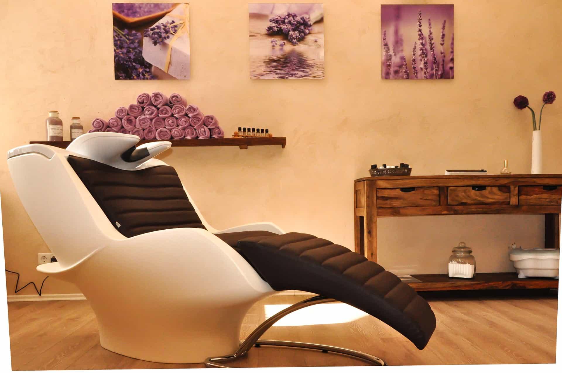 Salão de cabeleireiro decorado em bege, marrom e roxo, com lavatório em primeiro plano.