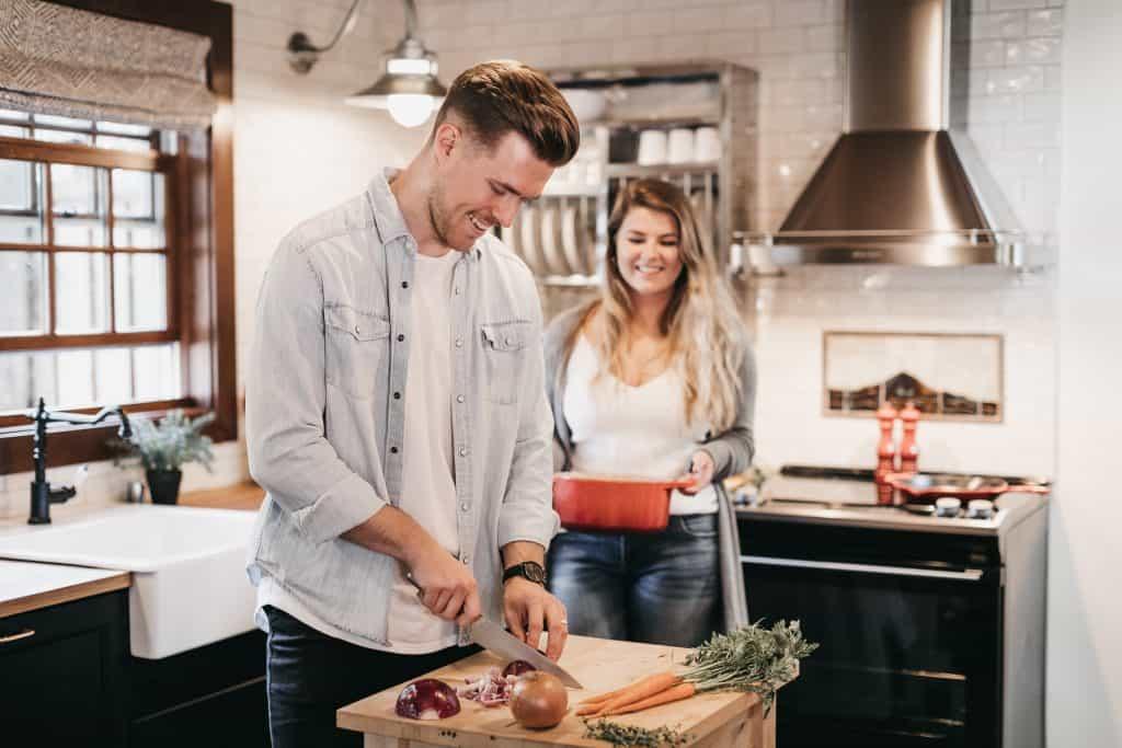 Imagem de um casal preparando uma refeição.