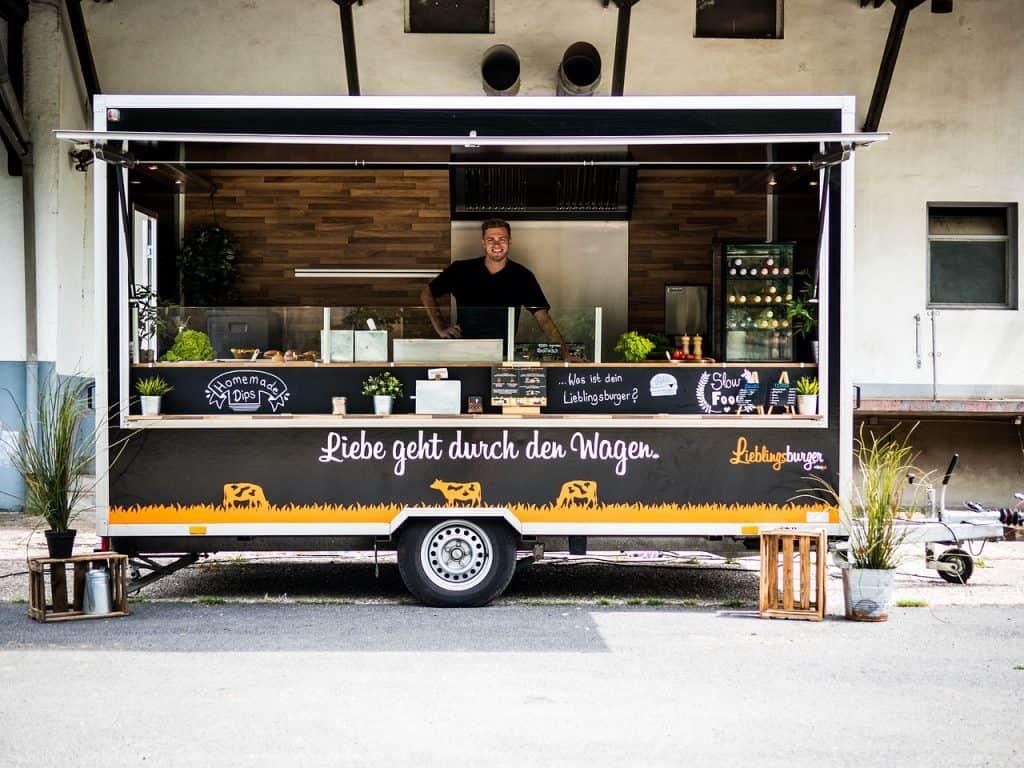 Na foto um food truck com um homem dentro.
