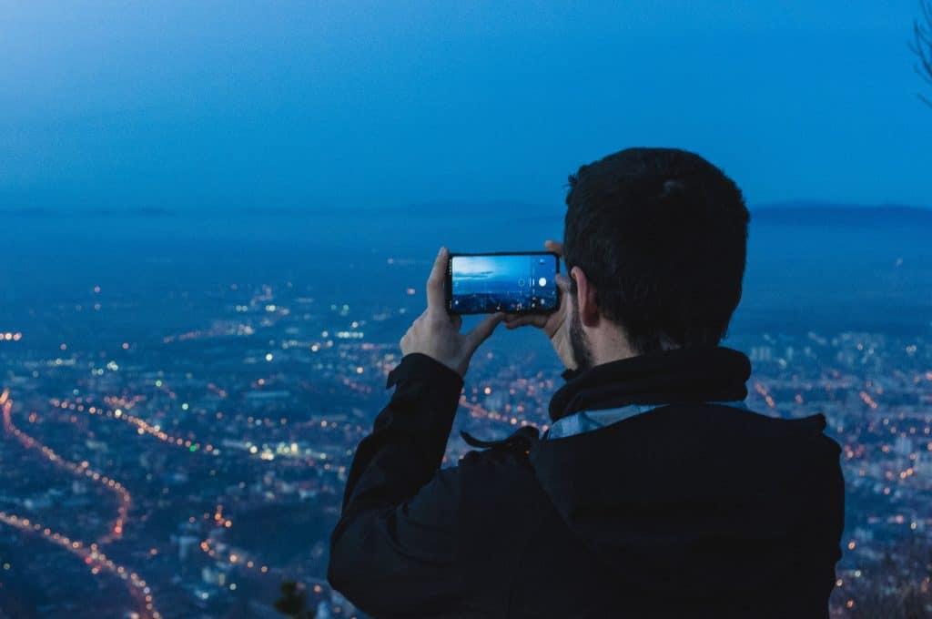 Imagem de um homem tirando uma foto a noite.