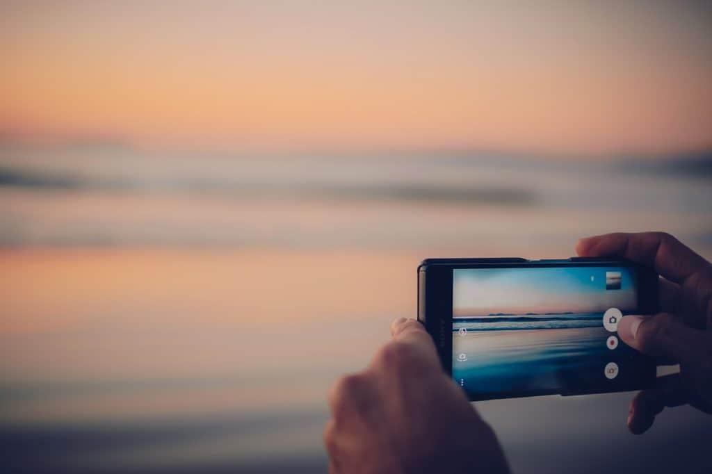 Imagem mostra uma pessoa segurando um celular e tirando foto do mar.