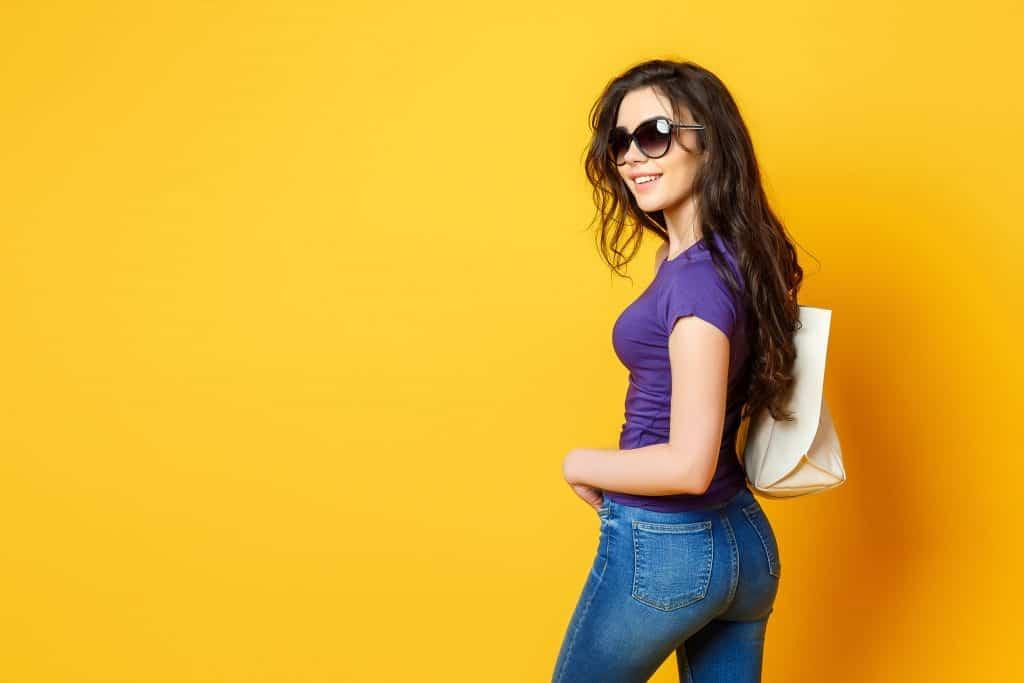 Mulher de cabelos pretos, calça jeans, blusa roxa, óculos de sol e bolsa em um fundo amarelo.