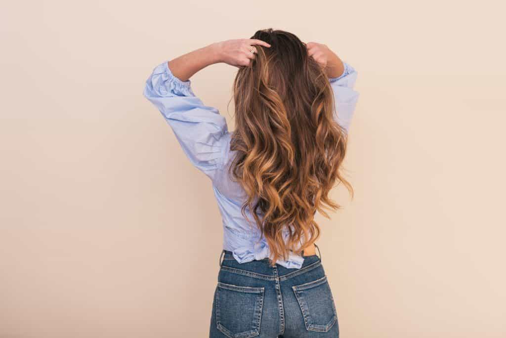 Imagem de uma mulher mexendo nos cabelos.