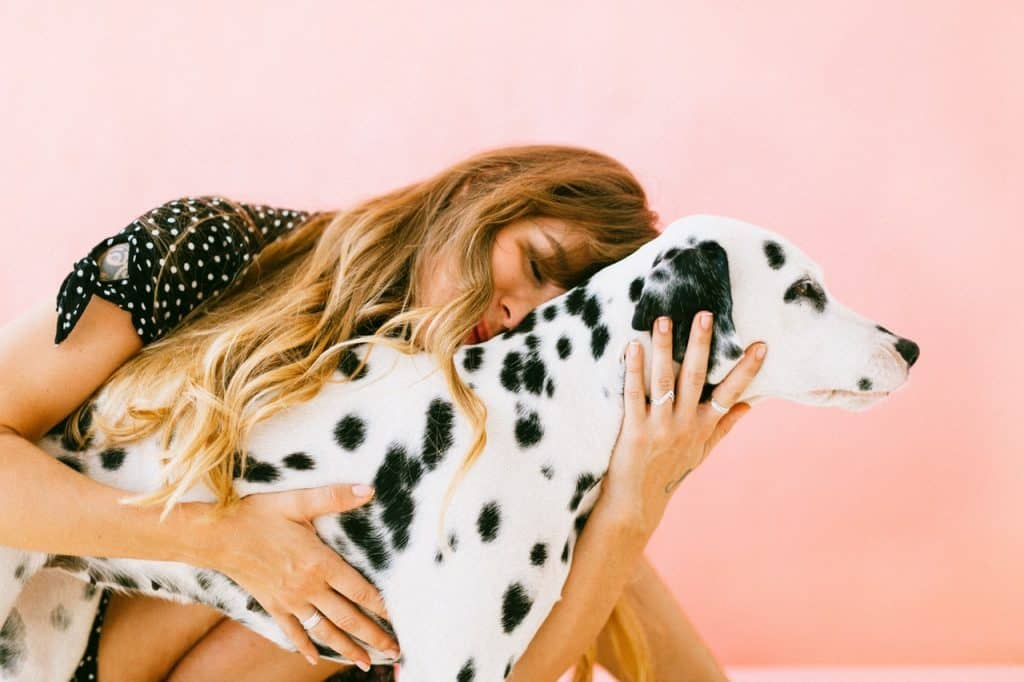 Image of a woman hugging a dog.