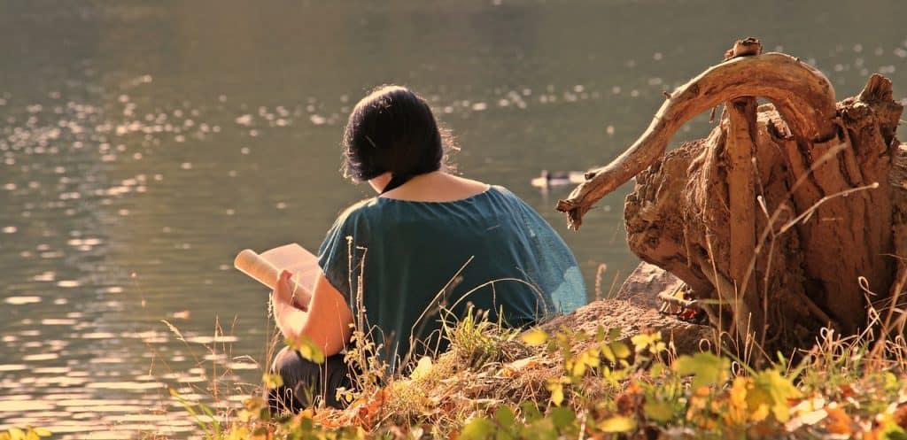Mulher lendo livro na beiro de rio.