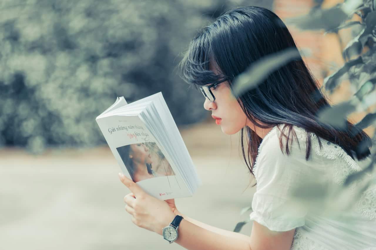 Imagem de uma moça lendo um livro.