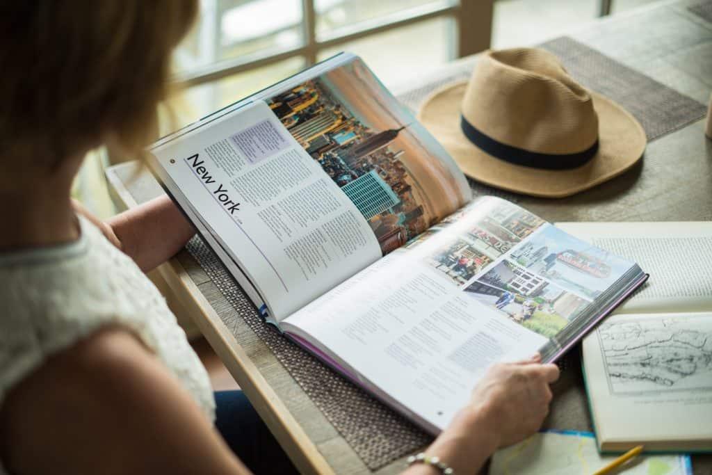Imagem de uma mulher lendo um livro de viagens.