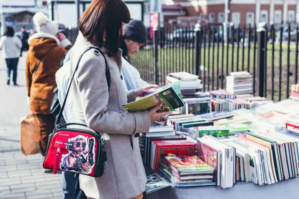 Imagem de uma mulher escolhendo um livro em uma banca de rua.