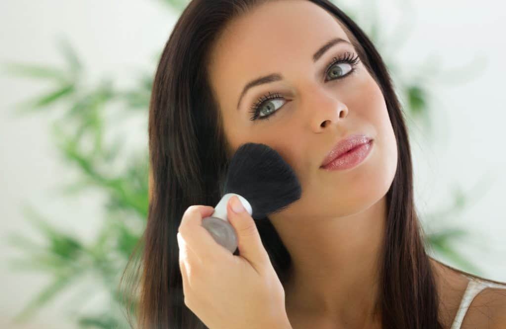 Jovem mulher finalizando maquiagem com pincel.
