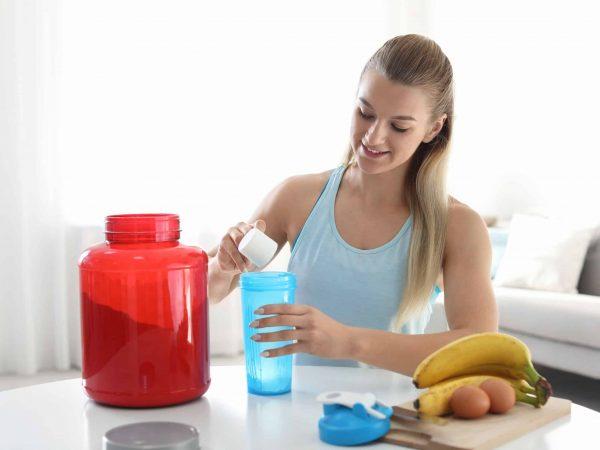 Imagem de uma mulher preparando um suplemento.