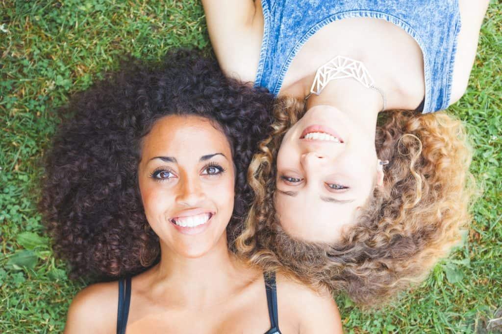 Moças de cabelo loiro cacheado e preto cacheado deitadas lado a lado.