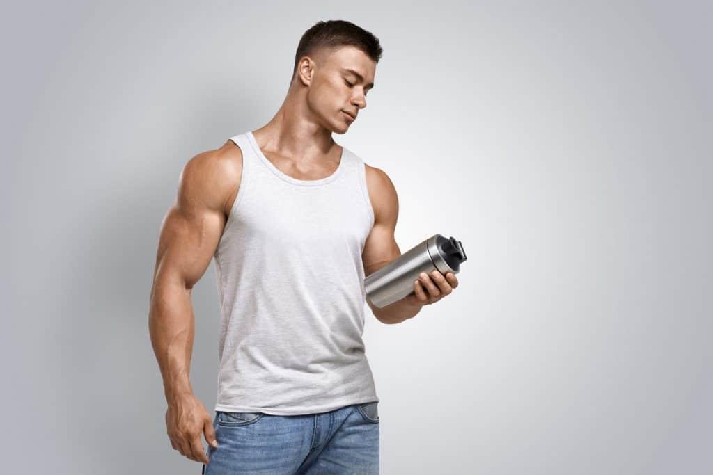 Imagem de um homem musculoso segurando uma coqueteleira.