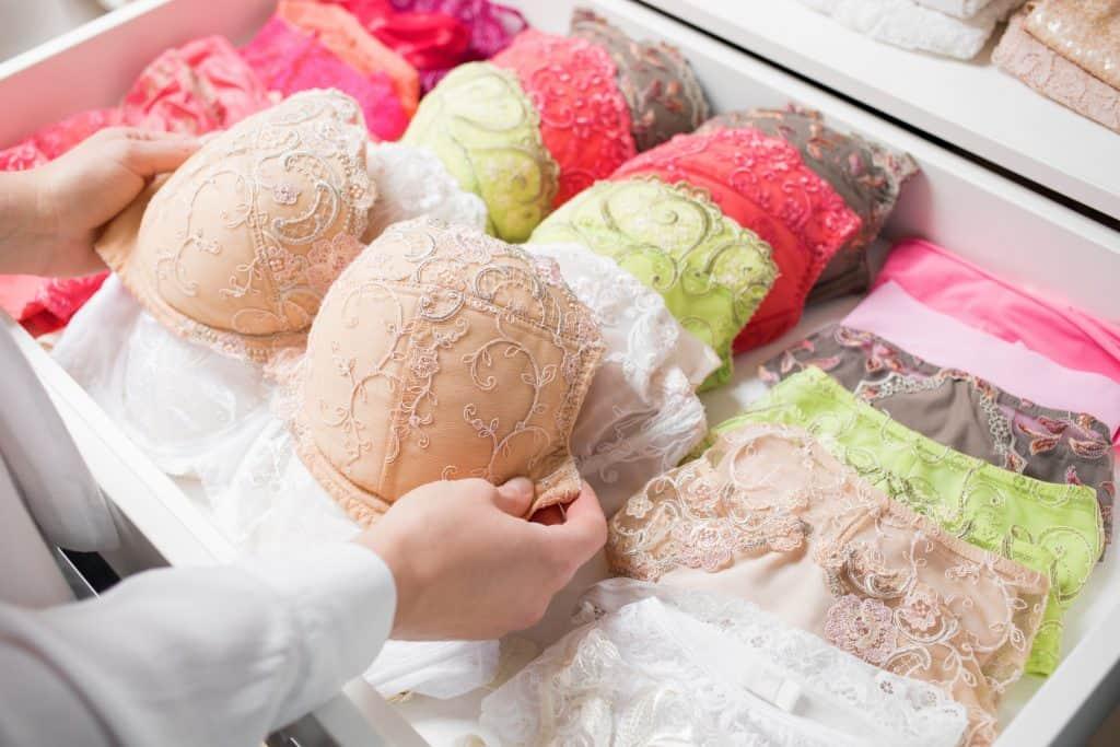 Foto de duas mãos femininas organizando uma gaveta com sutiãs e calcinhas rendadas e coloridas.