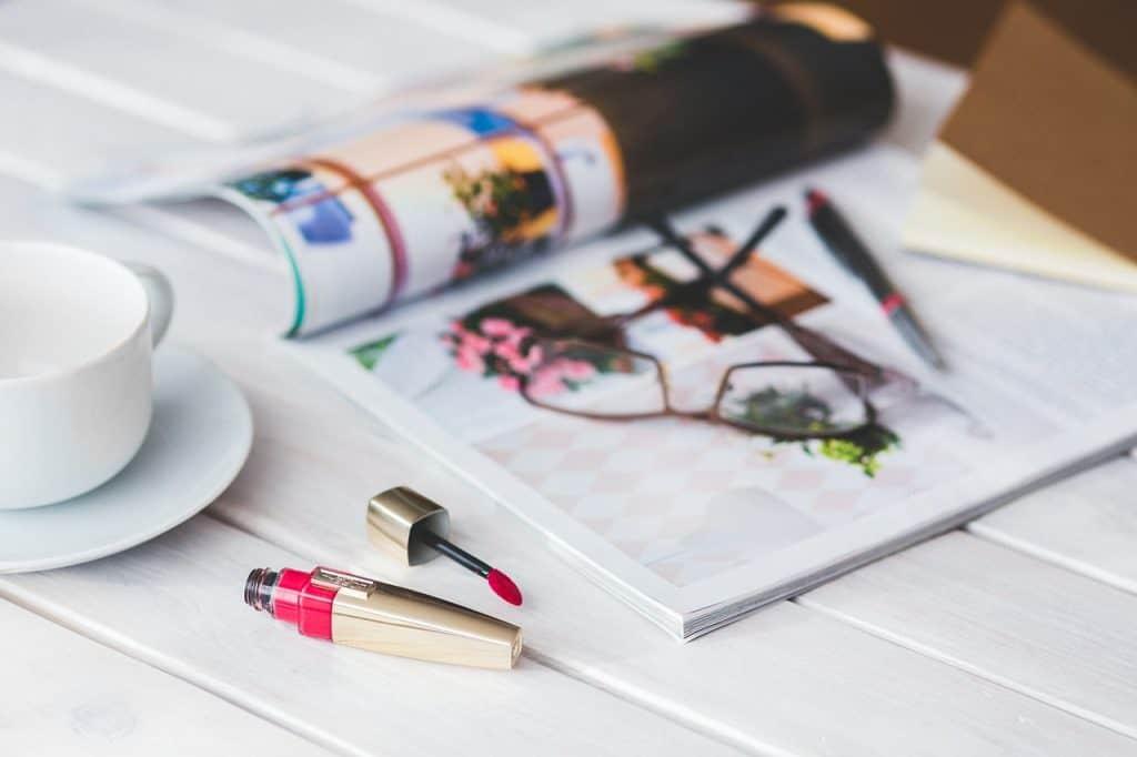 Imagem de um gloss labial em cima de uma mesa.