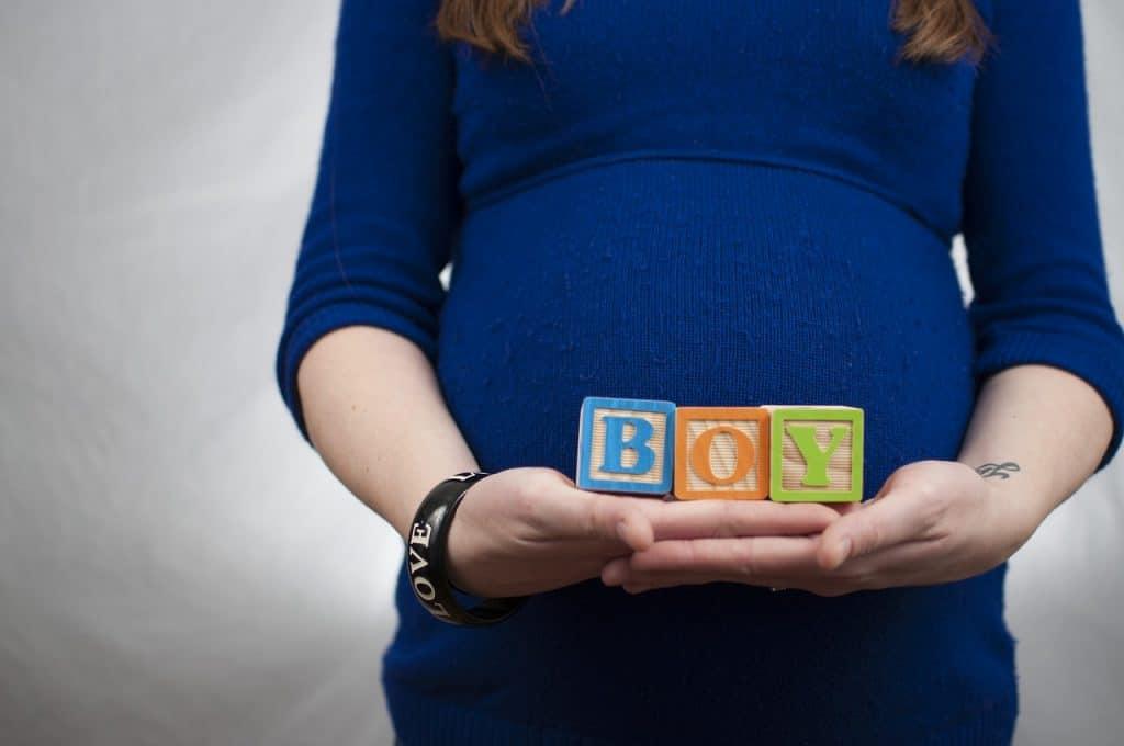 Na foto uma mulher grávida segurando cubos que formam a palavra boy.