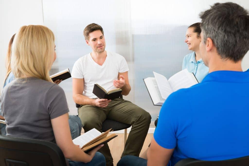 Imagem de várias pessoas reunidas em círculo, sentadas em cadeiras, com livros nas mãos, enquanto sorriem e olham para o homem que está na frente explicando algo.