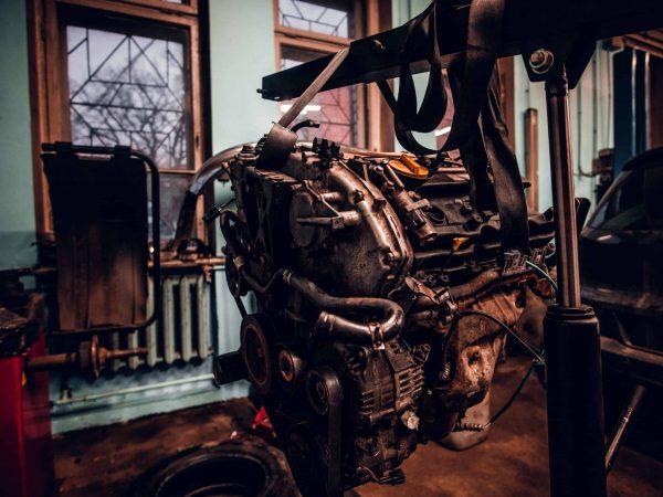 Imagem mostra um guincho hidráulico levantando partes de um carro.