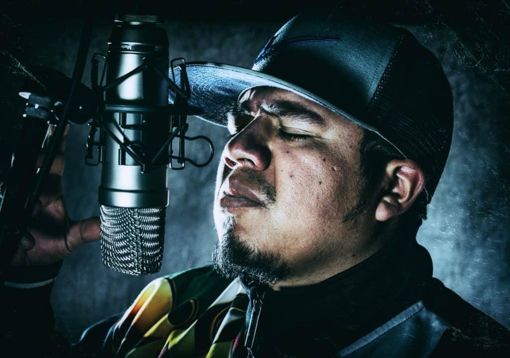 Imagem mostra um homem, com um boné da Nike, expressando emoção enquanto canta muito próximo de um microfone de estúdio.