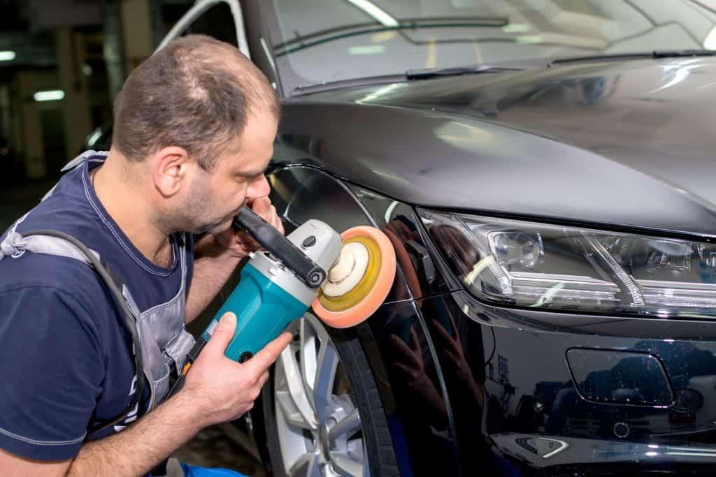 Imagem mostra um homem usando uma politriz na lateria de um automóvel.
