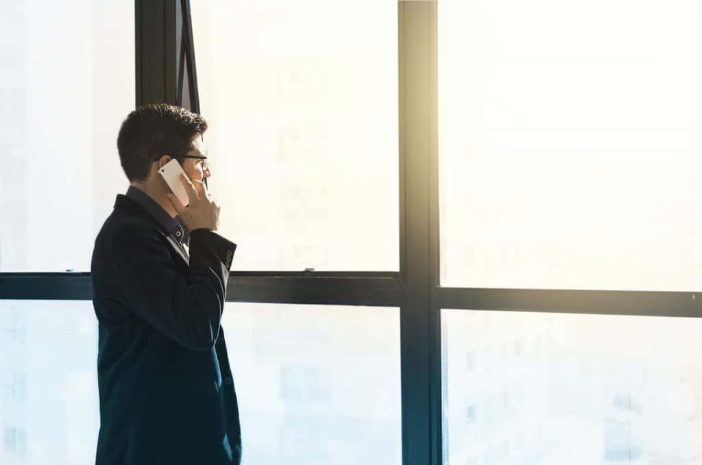 Homem em pé falando ao celular.