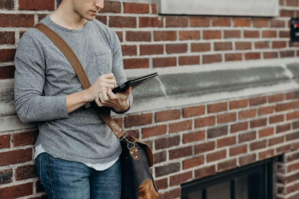 Na foto um homem encostado em uma parede de tijolos usando um tablet.