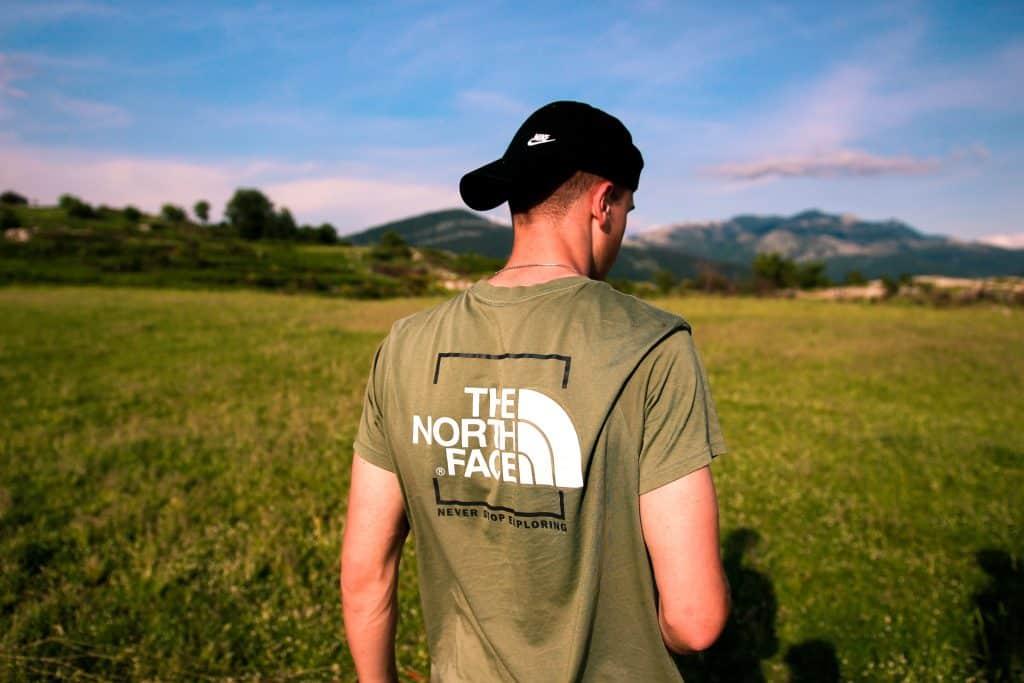 Imagem mostra uma pessoa, de costas para a câmera, usando um boné Nike com a aba para trás, olhando para um extenso gramado, mostrado em segundo plano, desfocado.