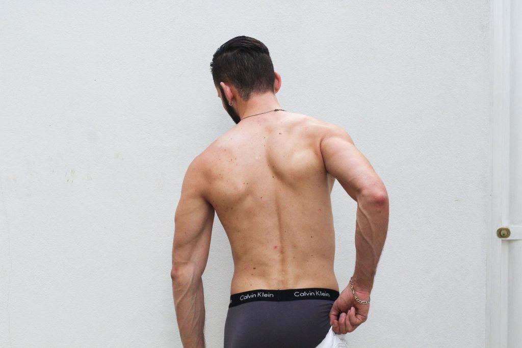 Imagem mostra um homem de costas vestindo uma cueca boxer.