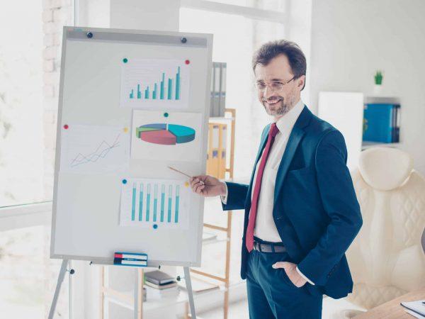 Na foto um homem fazendo uma apresentação com um flip chart.