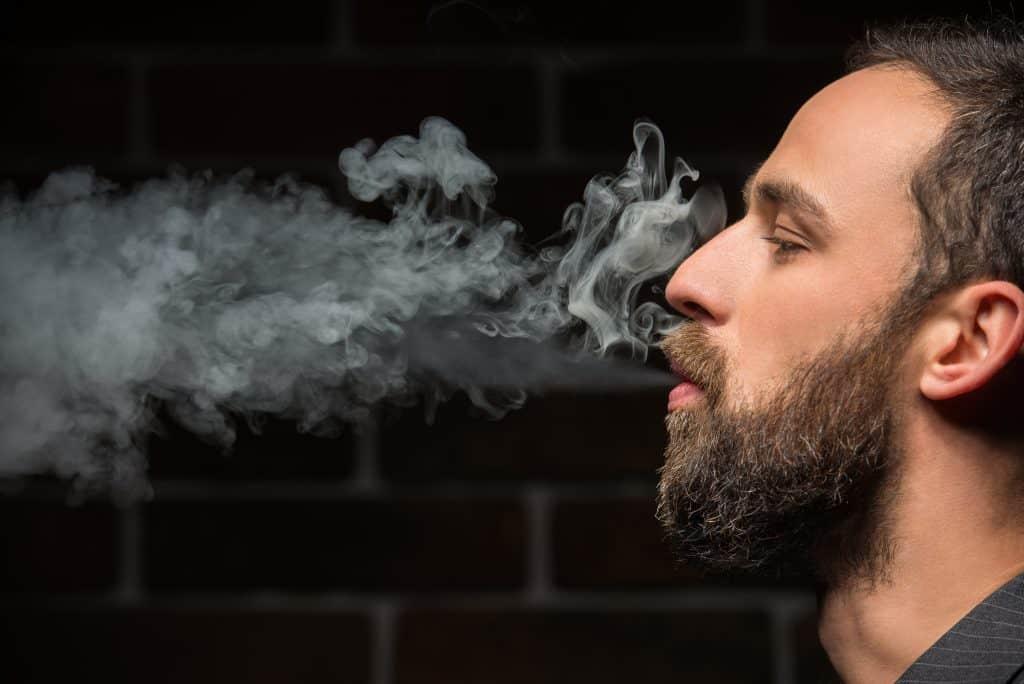 Imagem mostra um homem soltando a fumaça de um cigarro.