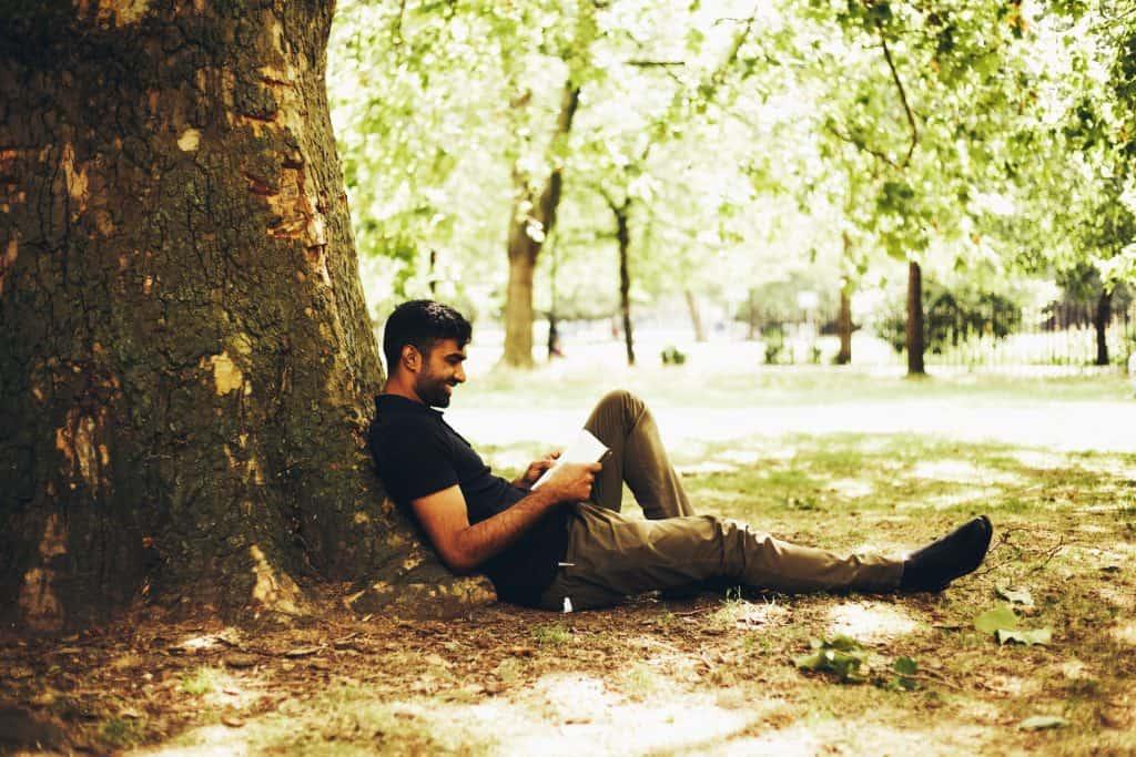 Homem lendo apoiado em árvore.