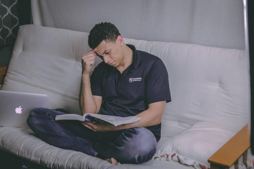 Um homem sentado de pernas cruzadas em um sofá branco está segurando um livro aberto, apoiado pelas pernas, enquanto leva uma das mãos à cabeça.